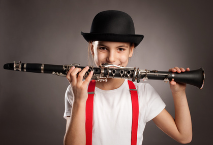 little girl playing clarinet on a gray background