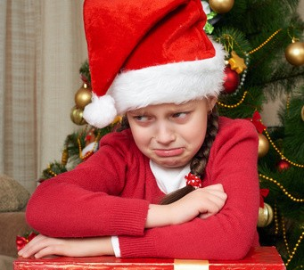 Unhappy girl crying near christmas tree, dressed in red and santa hat